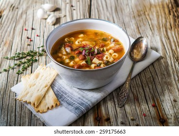 A bowl of minestrone soup with crackers on rustic/ vintage background