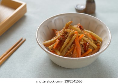 a bowl of miso kinpira gobo (burdock root) with carrot sprinkled with dried chili and sesame seeds