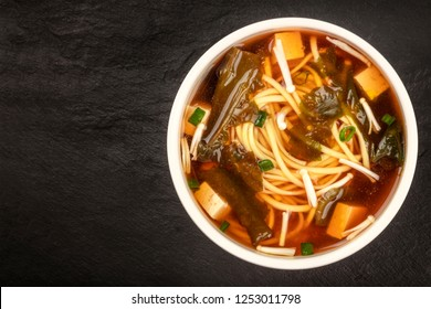 A bowl of miso soup with tofu, scallions, noodles, wakame, and enokitake mushrooms, shot from the top on a black background with a place for text