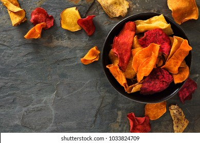 Bowl of mixed healthy vegetable chips. Top view, corner orientation with copy space on a dark stone background.