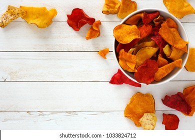 Bowl of mixed healthy vegetable chips. Top view, corner orientation with copy space on a white wood background.