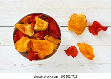 Bowl of mixed healthy vegetable chips. Top view, still life on a white wood background.