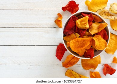 Bowl of mixed healthy vegetable chips. Top view, side orientation with copy space on a white wood background.