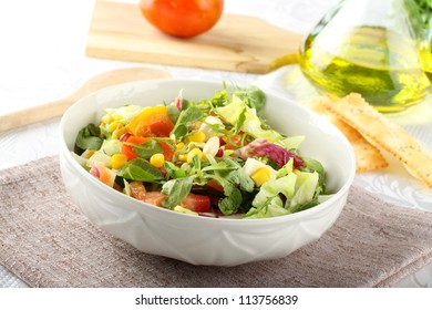 Bowl of mixed salad on complex background