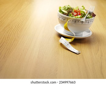 A bowl of mixed salad with a tape measure for healthy eating on a wooden background with copy space.