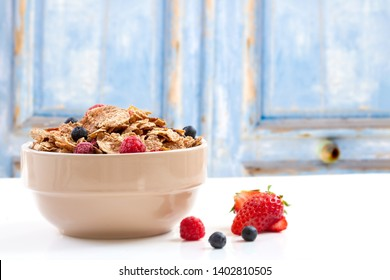 A bowl of muesli breakfast cereal and milk with berries blue wood background
