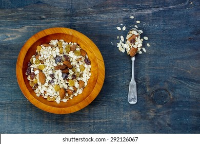 Bowl of muesli for healthy breakfast over dark wooden background. Health and diet concept.
