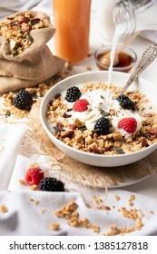 Bowl of muesli with milk and berries and a glass of fruit juice.