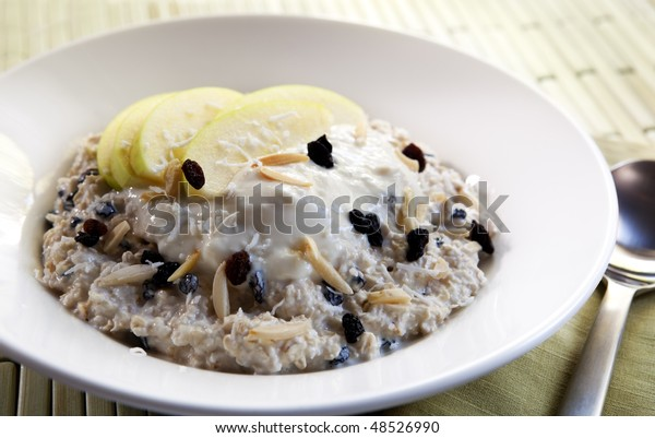 Bowl of muesli with yoghurt.  Bircher muesli made with oats, apples, currants, flaked almonds, currants, and shredded coconut.