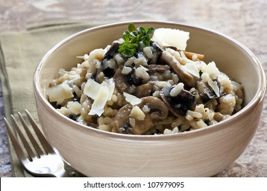 Bowl of mushroom risotto, garnished with thyme and parmesan.