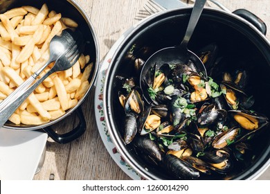 A bowl of mussels with French fries