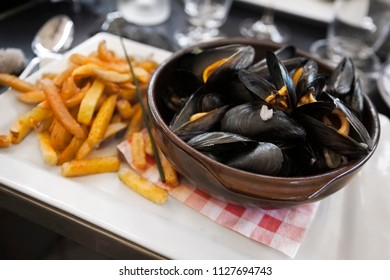 Bowl of mussels and potato fries in a French bistro