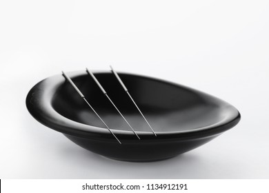 Bowl with needles for acupuncture on white background