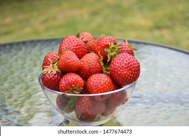 Bowl with newly picked strawberries on a table