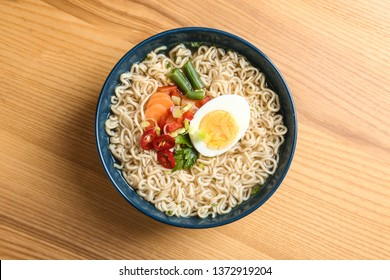 Bowl of noodles with broth, egg and vegetables on wooden background, top view