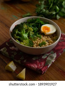 Bowl of noodles with vegetables and eggs, on top of red cloth and wooden table. Vegetables on table, rustic style. Veggie.