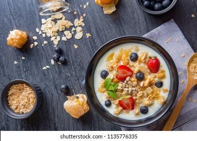 bowl of oat granola with yogurt, fresh blueberries, strawberries, blackberries and nuts with spoon on black wooden board for healthy breakfast, top view