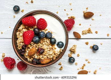 bowl of oat granola with yogurt, fresh raspberries, blueberries and nuts on white wooden board for healthy breakfast. top view