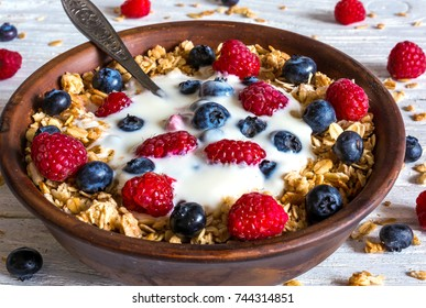 bowl of oat granola with yogurt, fresh raspberries, blueberries and nuts with spoon on rustic wooden board for healthy breakfast, close up