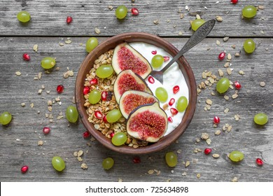 bowl of oat granola with yogurt, pomegranate seeds, figs, grapes and nuts with a spoon on rustic wooden board for healthy breakfast, top view