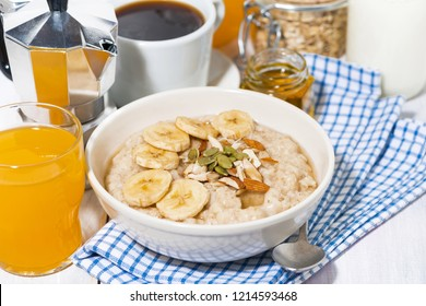 bowl of oatmeal with banana, honey and nuts for breakfast, closeup