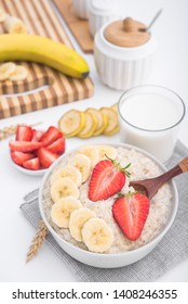 Bowl with oatmeal, banana and strawberry on a table. Sweet morning breakfast.