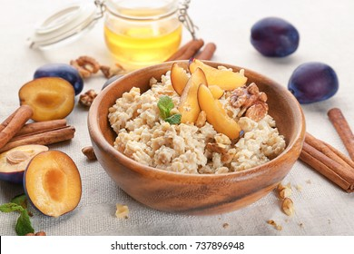 Bowl with oatmeal, fresh plums and nuts on table
