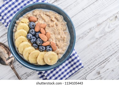 Bowl of oatmeal porridge with banana, blueberries, almonds, on wooden background, hot and healthy food for Breakfast, top view, flat lay