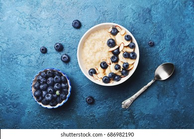 Bowl of oatmeal porridge with banana and blueberry on vintage table top view in flat lay style. Hot breakfast and homemade food