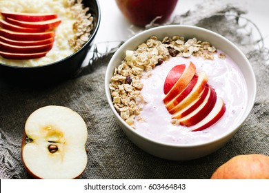 Bowl of oatmeal porridge with blueberry yoghurt, milk and muesli  with an apple on concrete background. Healthy food  or breakfast. lifestyle concept. Close up