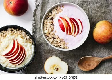 Bowl of oatmeal porridge with blueberry yoghurt, milk and muesli  with an apple on concrete background. Organic healthy food  or breakfast. lifestyle concept. top view