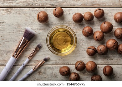 Bowl with oil, macadamia nuts and brushes on wooden table