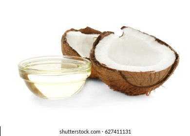 Bowl with oil near fresh coconut on white background