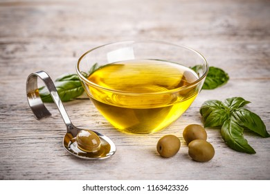 Bowl with olive oil and olives on wooden background