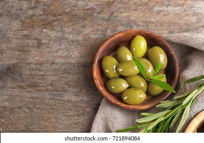 Bowl with olives on wooden table