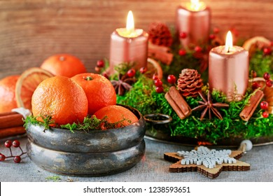Bowl with oranges among Christmas decorations. Advent wreath with four candles in the background.