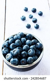 Bowl of organic blueberries on white wooden background. Selective focus. Concept for healthy eating and nutrition.
