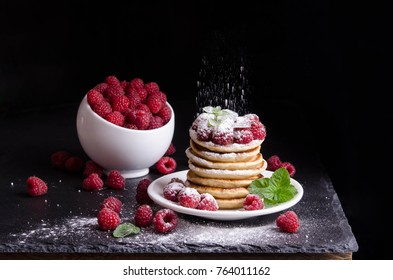 Bowl and  Pancakes with raspberries around on black backgound