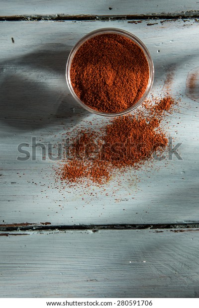 bowl of paprika on a wooden background