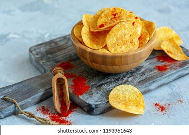 Bowl of paprika potato chips and a wooden scoop of ground paprika on an old serving board, selective focus.