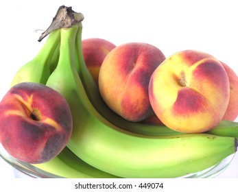 Bowl of peaches and banana on white background