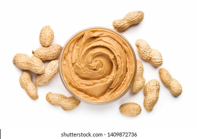 Bowl of peanut butter and unshelled scattered peanuts on white background, isolated