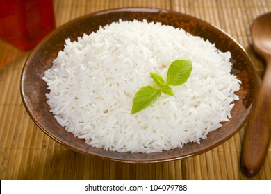 A bowl of perfectly cooked, plain Basmati rice, in an Asian style bowl, with a garnish of Thai Basil.