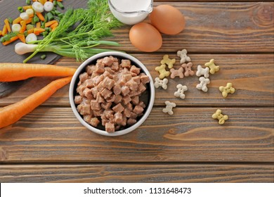 Bowl with pet food and natural products on wooden background