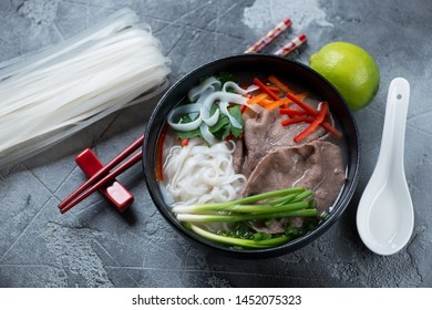 Bowl of pho bo soup with beef meat, high angle view over grey concrete background, studio shot