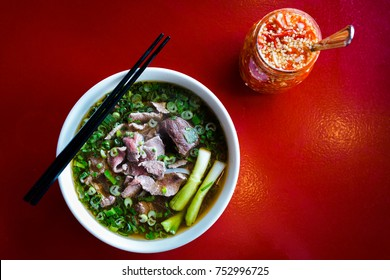 Bowl of pho tai (brisket) and a jar of chili vinegar.