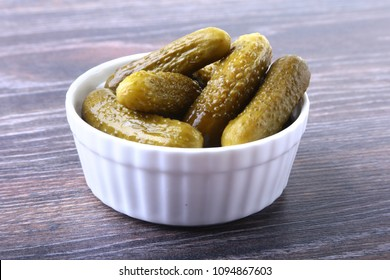 Bowl with pickled gherkins, cucumbers on wooden background close up. Pickles.
