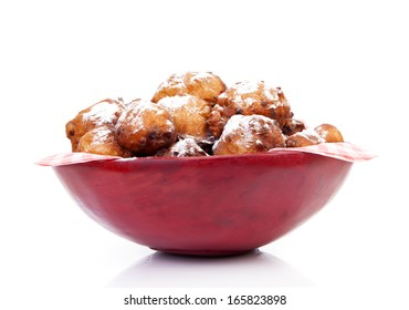 Bowl with Pile of Dutch donut also known as oliebollen, traditional New Year's eve food isolated on white background