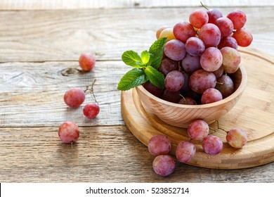 Bowl with pink grapes on a wooden stand.
