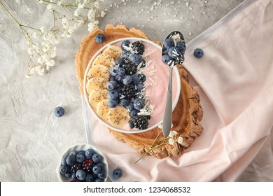 Bowl with pink yogurt and fresh fruits on light table